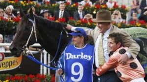 Jockey Luke Nolen (r) hugs Black Caviar's trainer Peter Moody after his win
