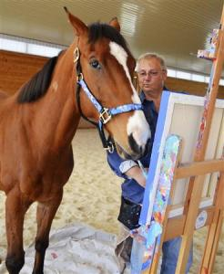 Metro, a 10-year-old retired bay thoroughbred horse wields a paintbrush as owner Ron Krajewski looks on at Motter's Station Stables in Rocky Ridge
