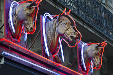 Three horses' heads are displayed above a horse meat butcher shop in Paris in February. French law enforcement officials said Monday that 21 people have been arrested in raids across the south of France targeting the trafficking of horse meat that were treated with laboratory antibiotics and weren't fit for human consumption. Jacques Brinon/AP/File