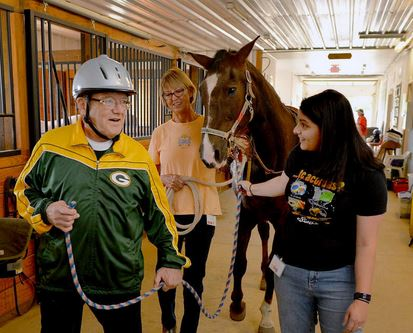 Balmoral Memory Care Center resident John Wilcox, right, and intern Emily Jayne, center, take Shiloh for a walk at Equestrian Connection in Lake Forest Wednesday afternoon. | Brian O'Mahoney/For Sun-Times Media